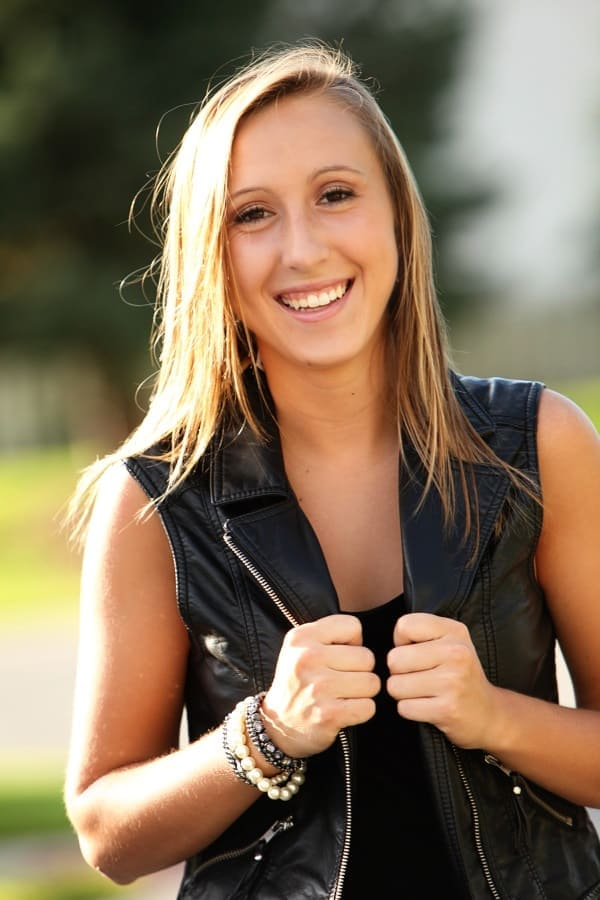 Young woman wearing leather sleeveless jacket, smiling at the camera