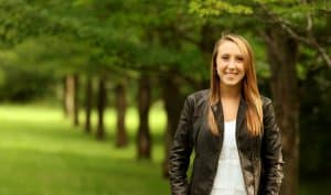 Young woman in leather jacket and white shirt, standing front of a row of trees, facing camera, smiling