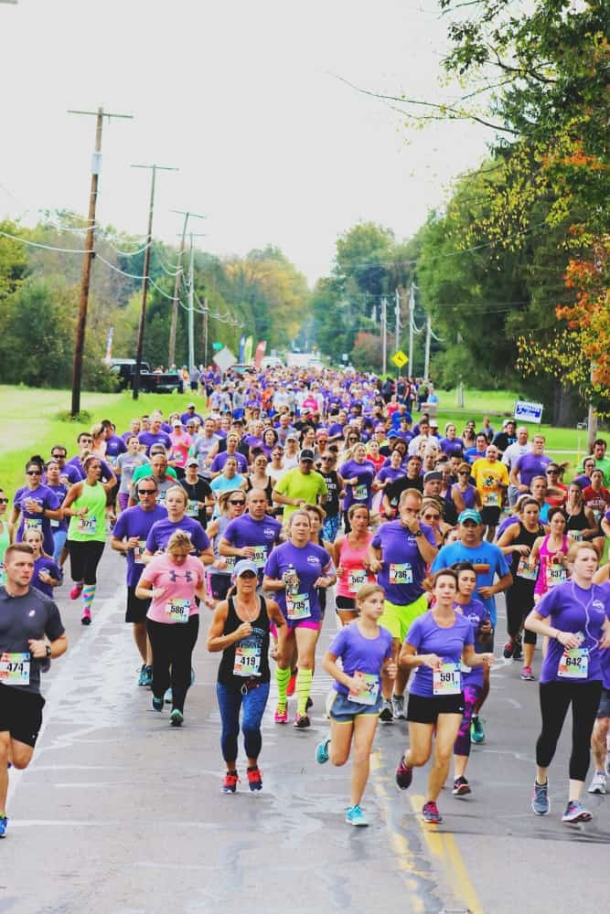 Large crowd of people, many wearing purple shirts and placards, running in a race on a paved street