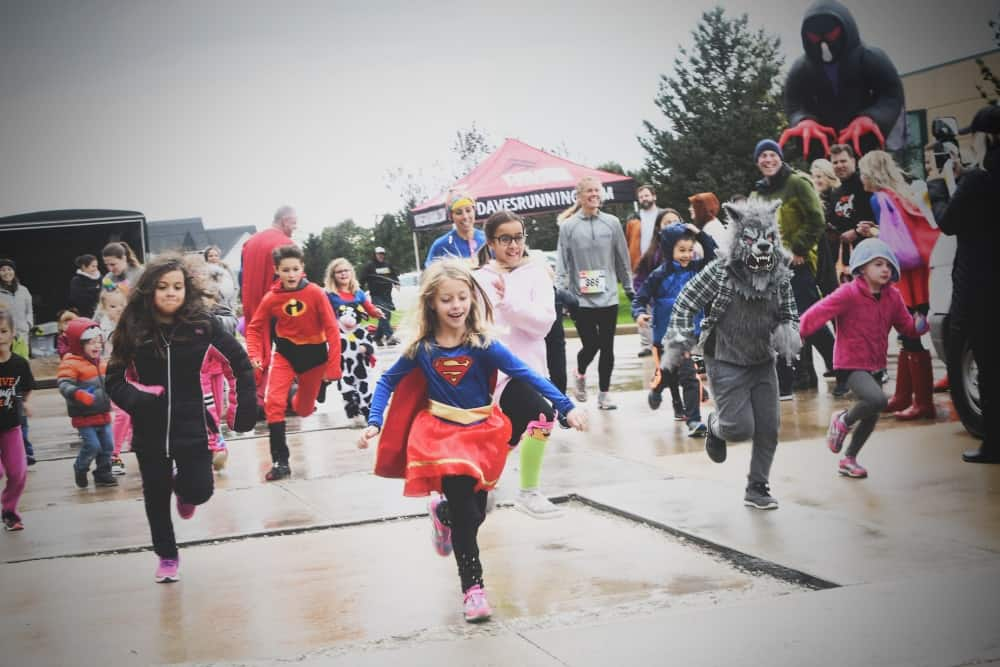 Children in Halloween costumes running a race. In the foreground, a young girl dressed as Superwoman smiles.