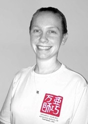 Young adult woman in white t-shirt, smiling at camera, grey background